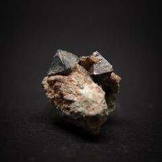 Yttropyrochlore-(Y), (Y,Na,Ca,U)1-2(Nb,Ta,Ti)2(O,OH)7 , South Cheyenne Creek, Cheyenne District (St. Peters Dome District), El Paso Co., Colorado, USA. Octahedral crystals of gray Yttropyrochlore-(Y) and red-brown zircon on granite. Yttropyrochlore crystal about 7 mm