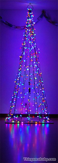 Photo of a cone-shaped string of Christmas lights running from floor to ceiling, aglow.