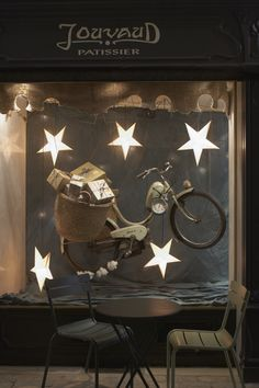 Vintage bike carrying brown paper packages under star lanterns. Pâtisserie Jouvaud: La vitrine de Noël