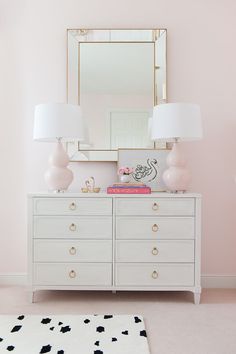 white dresser with black and white spotted rug and pink walls