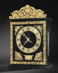 A GILTBRONZE MOUNTED EBONISED PEAR MANTEL CLOCK, LOUIS XIV, ATTRIBUTED TO BALTHAZAR MARTINOT le cadran à chiffres romains et arabes, dans une boîte rectangulaire ornée d'écoinçons, d'une frise de rinceaux et d'un fronton en bronze doré; Haut. 45 cm, larg. 31 cm, prof. 13 cm / Height 17 3/4 in; width 12 1/4 in; depth 5 in