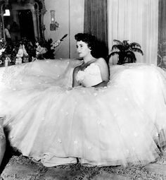"Photo of Elizabeth Taylor lounging in the silk and tulle gown that she donned for her role as debutante Angela Vickers in the film ""A Place in the Sun"" (1951). Costume designed by Edith Head. From Profiles in History."