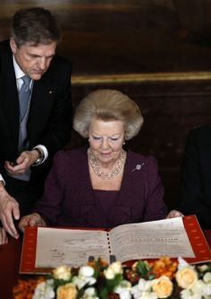 Queen Beatrix of the Netherlands looks over the Act of Abdication during a ceremony in the Moseszaal at the Royal Palace on 30 April 2013 in Amsterdam
