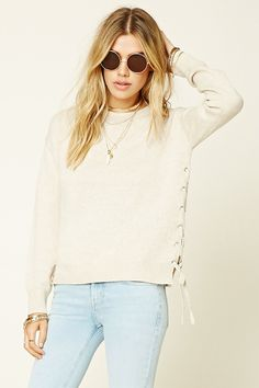 A heathered knit sweater top featuring lace-up sides, round neckline, dropped…