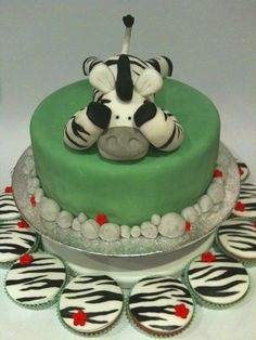 Green zebra Cake with zebra on top.. and cupcakes.