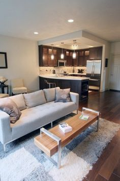 Open concept living room and kitchen layout with dark hardwood floors
