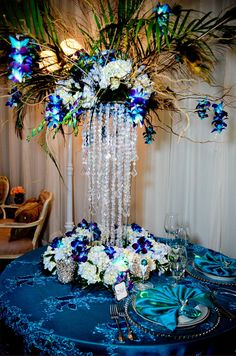 Extravagant Peacock tropical wedding centerpiece inspiration, tall crystal drape over hydrangeas with orchids in vibrant hues of purple and blue | Planned 2 Perfection