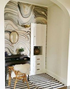 A marbled paper accent wall adds visual interest to a neutral space.