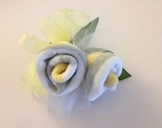 Perfect for a baby boy baby shower,this unique baby shower corsage is made with 2 pair of baby socks and Daddys boutonniere is made with 1 pair of socks! We added a pretty bow, some tulle to make it pretty. Add a wrist band or use your baby sock corsage as a pin on. The mommy and daddy to be is sure to be very happy at her baby girl or boy baby shower. Then after the baby shower take your baby sock baby corsage and boutonniere apart and you have baby socks for the newborn baby.