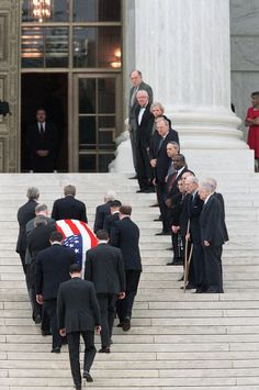 Past and present members of the Supreme Court, right, line the stairs as the coffin of retired Chief Justice Warren Burger is carried into the Court on in June 1995.