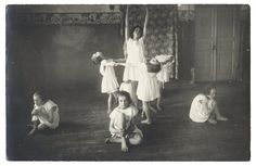 At the Jewish Children's Home. Barefoot girls in white dresses pose in a dance tableau in a room with floral wainscoting and a decorative wall-hanging. Kaunas, circa 1925.
