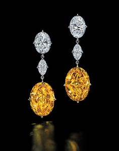 'THE ORIENTAL SUNRISE'. A unique and rare pair of diamond and coloured diamond earrings. Each fancy vivid orange-yellow oval-cut dia., weighing 12.20 and 11.96 cts, to the marquise-cut D/VS2 dia. link, weighing 0.73 ct each, and oval-cut D/VS2 dia. surmount, weighing 3.03 and 3.02 cts, 4.5 cm, mounted in gold. Price Realised USD 11,598,087 // Estimate USD 9,735,648 - USD 12,810,064. GIA / 12.20 cts - Fancy Vivid Or.-Yell./VVS2 // 11.96 cts - Fancy Vivid Or.-Yell./VS1 [C. 18 May 2016 - GE.]