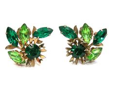 Vintage mid-century emerald- and peridot-green rhinestone clip-on earrings Large 1-1/2 by 1-1/2 size, but lightweight Flower with leaves in a goldtone setting Rhinestones are all prong set 1950-60s costume jewelry Excellent vintage condition with no damage. Clips are firm. Ready to wear with your retro and vintage fashions! The green rhinestones would fit in well when worn with your vintage fashions at all the Christmas parties, dancing, dinners, and such! And dont forget to w...