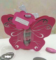 Contenant à dragées papillon couleur rose fuchsia, vu de dos avec son étiquette de forme fleur et de couleur identique. Sur celle-ci sont précisés les prénoms des mariés et la date du jour J. Ecriture en harmonie avec la couleur du ballotin. http://www.maison-des-delices.fr/contenants-a-dragees-mariage-transparent-464