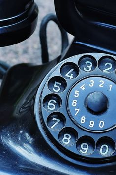 Black Rotary Telephone at Top of Gray Surface
