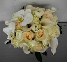 Bridal bouquet featuring calla lilies, roses, ranunculus, garden roses, and phalaenopsis orchids by Studio AG