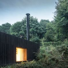 Blackened timber house extension hidden  in the forest by Marchi Architectes/ Normandy, France