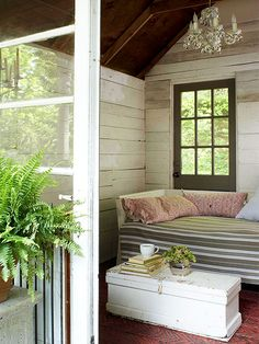 Outdoor Getaway - A chicken-coop-turned-teahouse became a sheltered retreat for enjoying garden views and fresh breezes, thanks to an old daybed covered with outdoor ticking fabric. An electric chandelier adds romance and allows the space to function after dark.