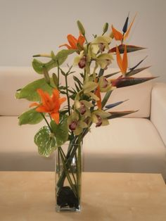 Anthurium, cymbidium orchid and bird of paradise vase arrangement.