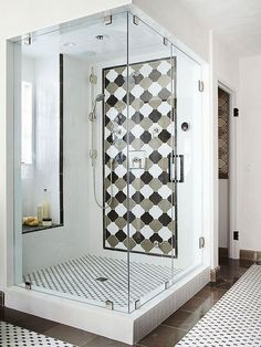 Add a seat beneath a window so you can enjoy natural light, views, and, in this case, comfortable proximity to handheld sprays. This high-style walk-in shower houses a tiled window alcove that boasts a marble-capped seat, which takes its cue from black accent tiles that pop on shower walls and floors.