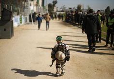 A Palestinian boy wearing a military costume arrives at a military-style graduation ceremony for Palestinian youths who were trained at one of the Hamas-run Liberation Camps, in Gaza City, January 29, 2015. REUTERS/Suhaib Salem