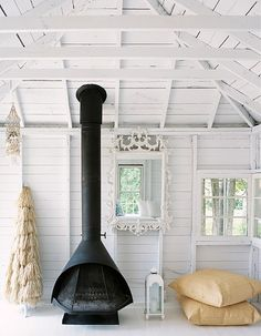 white walls. wood stove. beach house interior