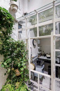 En el patio pintado de blanco de esta casa de pocos metros cuadrados de colegiales, una torre de hierro (Costado) repleta de plantas.