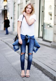 White V neck tucked into ripped skinny jeans, worn with ankle strap heels and a denim jacket wrapped around the waist