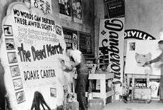 Painter Chauncey Curtis works on a silent film advertisement for a theater in Mankato, Minnesota, in the 1930s