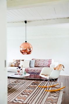 tom dixon copper pendant, kilim, eames rocker, floral sofa