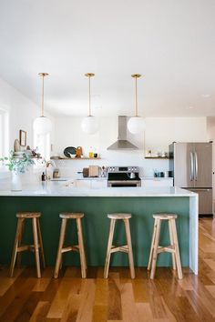 bright kitchen with warm wood floors, waterfall countertop, brass fixtures, and green accent below the bar