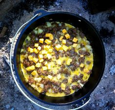 Mountain Man Breakfast Casserole cooked over hot coals in a Dutch Oven for a hearty and delicious breakfast perfect for a fun day camping!