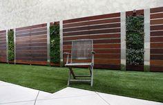 Комбинированный панельный забор из деревянных реек и металлических опор.