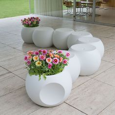 "Dimple will make you flip ... literally! Flipped on one side, it's a stool. Flipped to the other, it becomes the perfect planter. Its ""dimples"" on the side invite you to link them one to another, creating a connected winding row of multi-functional pods."