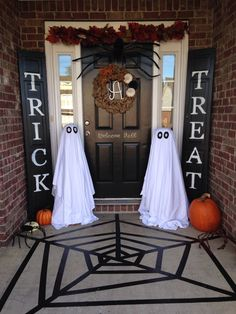Halloween porch! Painted bifold doors, black painters tape for the web, and tomato cage ghosts