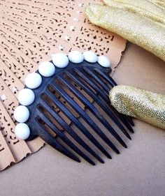 """Etsy: """"A mid Victorian dyed horn coronet hair comb with milk stone embellishment. It is made from black dyed natural horn and is adorned with nine pieces of so-called """"milk"""" glass forming roundels across the top of the curved heading.""""  3 ins h x 3¼ ins w"""