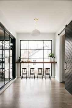 Coffee nook against a full wall window with a sliding barn door and wood and metal bar stools. Home Room Design, House Design, Kitchen Design, Home Bar Table, Cabin Coffee, Coffee Bar Design, Window Bars, Cocinas Kitchen, Kitchen Window Bar