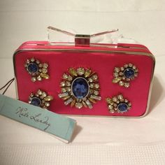 NWT Kate Landry Bejeweled Hot Pink Clutch W/ Strap Brand New With Tags. Beautifully embellished hot pink clutch. The top is adorned with a clear lucite/acrylic bow on top. This bow opens & closes this beautiful clutch! The silver chain strap is long enough to be used as a Cross-body,  but can be removed as well! Strap is removable  versatile clutch  NO TRADES / NO PAYPAL - Please submit an offer if you are interested! Measurements: 7.5 inches by 4inches Kate Landry Bags Clutches & Wristlets