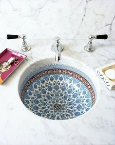 A beautiful sink makes a splash in an otherwise black and white bathroom