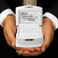 $18 Wooden chest style his and hers wedding ring box. The white wooden box measures 3 1/2 inches wide by 2 3/4 inches long by 2 inches tall. The hinged lid sports a small silver clasp complete with key to keep your ring box secure before and during your wedding ceremony. The white velvet inner lining is slotted to hold the bride and groom's wedding band.