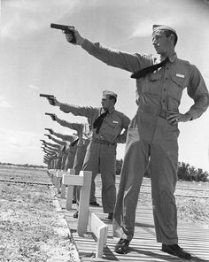 Naval Aviation Cadets from the Naval Air Station at the pistol range with Colt M1911-A1 .45 pistols Corpus Christi Texas United States circa 1941.