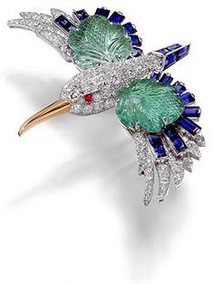 BROCHE PINZA MARTÍN PESCADOR CARTIER PARIS, 1941 Platino, oro amarillo, diamantes talla brillante y 8/8, dos esmeraldas grabadas con forma de hoja para un peso total de 17,66 quilates, zafiros facetados y calibrados, dos cabujones de rubí.