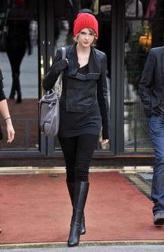 taylor swift wears a red beanie, black leather jacket and black boots obsessed with this.