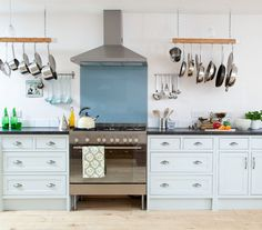 A really great stove can transform a kitchen. For a nice pop of color, consider a pretty splashback like a marine blue glass. To make a kitchen homey and high-functioning, hang storage racks from the ceiling for frequently used pots and pans.