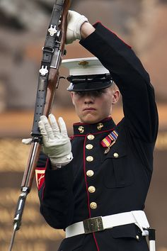 """Andrew Wingate, Silent Drill Platoon inspection team member, spins his Garand rifle in the """"long line"""" sequence during a Tuesday Sunset Parade at the Marine Corps War Memorial in Arlington, Va. Once A Marine, Marine Mom, Us Marine Corps, Marine Life, Men In Uniform, Us Marines Uniform, The Few The Proud, Military Life, Usmc"""