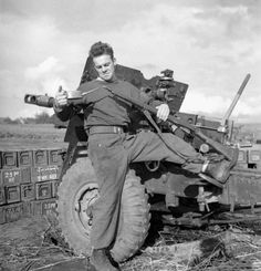 Bombardier A.E. Hollings of the 4th Field Regiment, Royal Canadian Artillery, oils his rifle; Ossendrecht, Netherlands - 23 October 1944