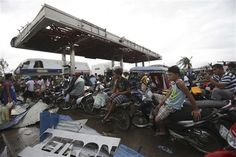 Survivor wait for gasoline at typhoon-ravaged Tacloban city, Leyte province, central Philippines on Tuesday, Nov. 12, 2013. Four days after Typhoon Haiyan struck the eastern Philippines, assistance is only just beginning to arrive. (AP Photo/Aaron Favila)