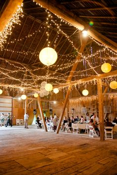 twinkle light and paper lanters barn wedding. Yes. All of that. And then picture the lanterns on each table with votive candles around. It's gonna be frickin magical.
