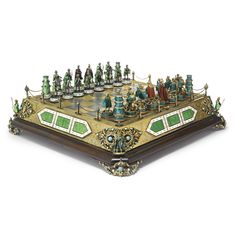 A Hungarian silver, enamel, and gem-set chess set, 20th century the board on wood plateau with enameled plaques at the sides and figures at the corners in front of scrolling foliage mounted with turquoises and pearls, the top lifting to store the pieces, one side enameled in light green coats, the bases painted with green foliage on white and set with garnets; the other side enemeled dark green and set with opals, the Kings and Queens with red cloaks
