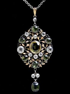 Arthur & Georgina Gaskin. A silver pendant with golden leaves and berries, set with a rare yellow chrysoberyl, green zircons and rock crystal.